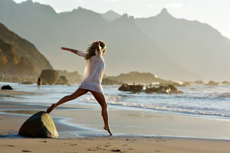 A jovem mulher que salta na praia no verão imagem de stock