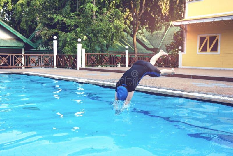 A jovem mulher que salta nas piscinas fotos de stock