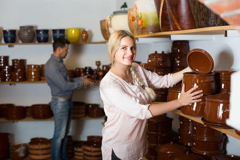 Jovem mulher que seleciona mercadorias do prato cerâmico na oficina fotografia de stock