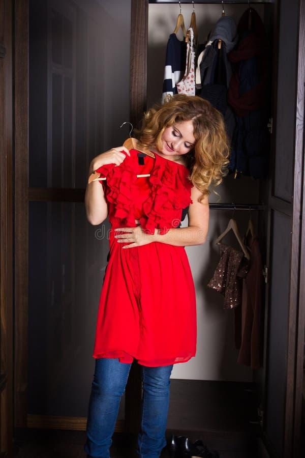 Jovem mulher que seleciona um vestido fotografia de stock royalty free