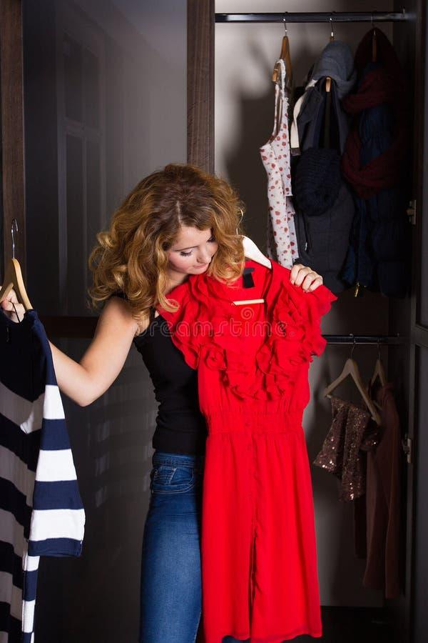 Jovem mulher que seleciona um vestido foto de stock
