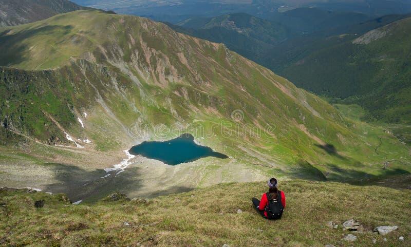 Jovem mulher que senta e que admira um lago bonito nas montanhas fotografia de stock royalty free