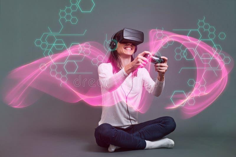Jovem mulher que senta e que tem o divertimento que joga um vid da realidade virtual fotos de stock