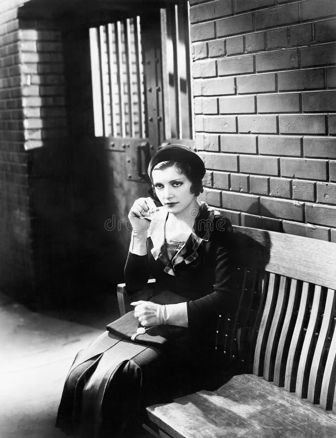 Jovem mulher que senta n um banco na frente de uma pilha de cadeia (todas as pessoas descritas não são umas vivas mais longo e ne fotografia de stock royalty free