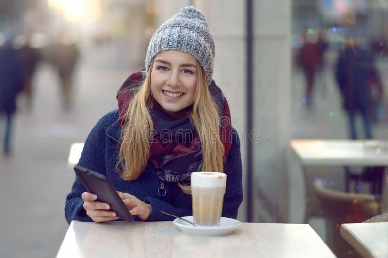 Jovem mulher que senta-se apreciando uma bebida fora fotografia de stock