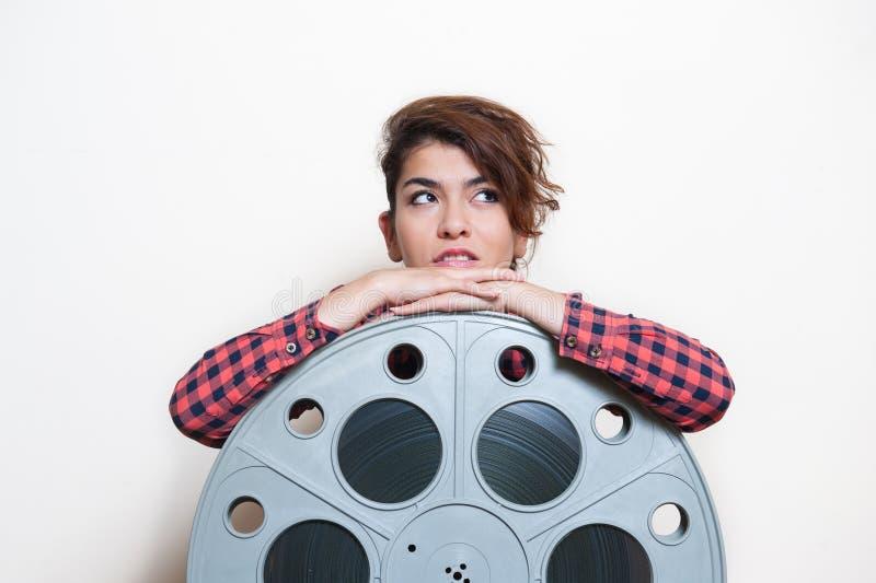Jovem mulher que senta-se atrás do carretel grande do filme do cinema imagens de stock