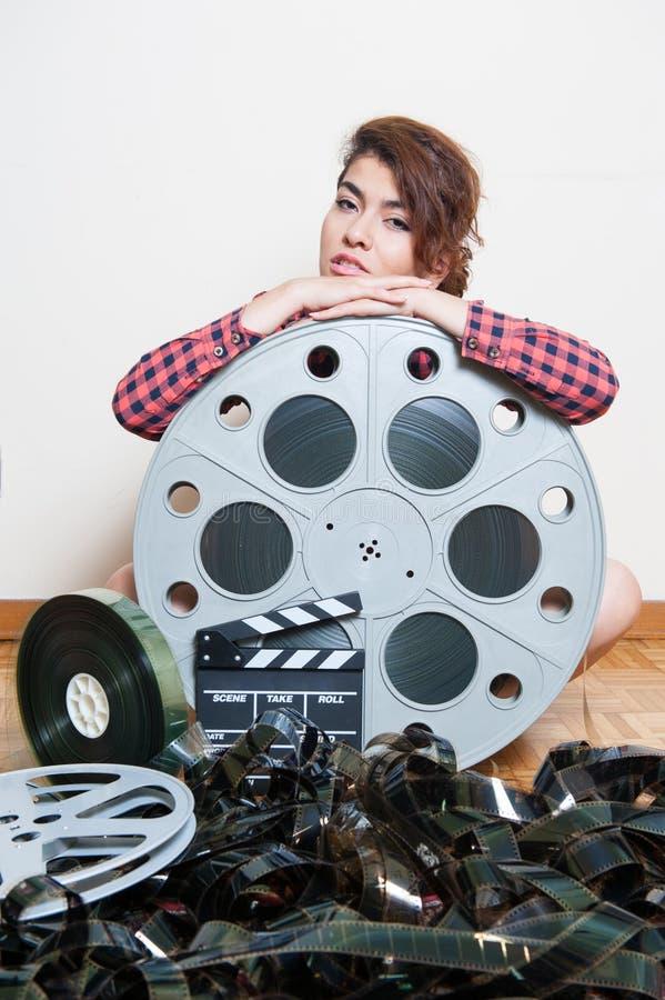 Jovem mulher que senta-se atrás do carretel grande do filme do cinema fotografia de stock royalty free