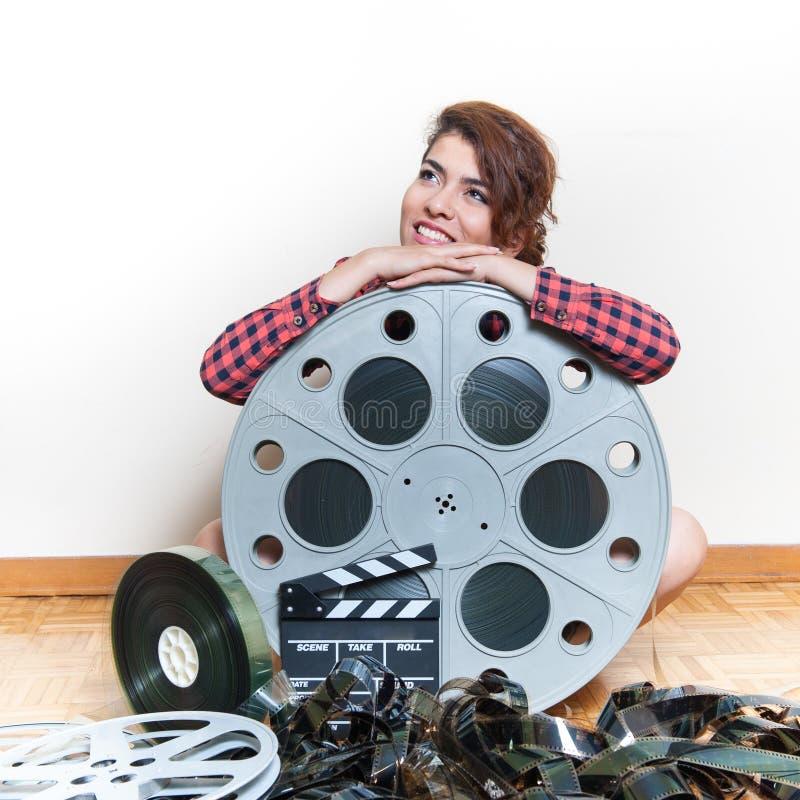 Jovem mulher que senta-se atrás do carretel grande do filme do cinema imagem de stock royalty free