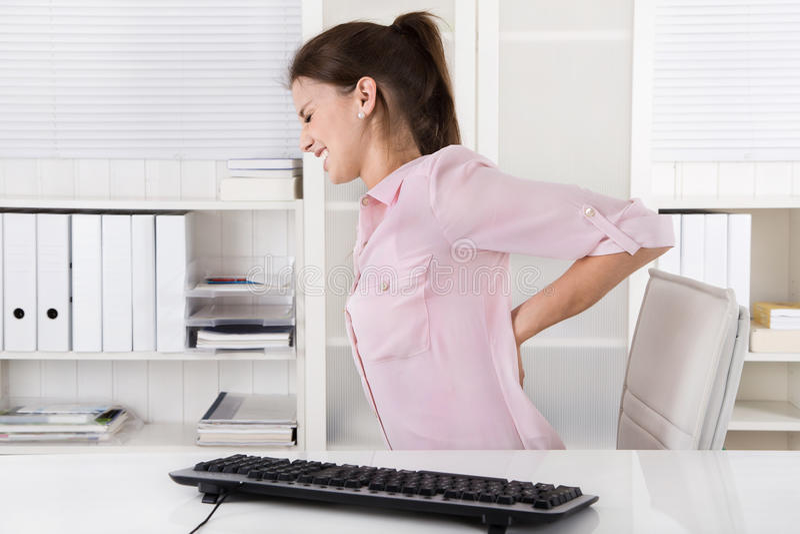 Jovem mulher que senta-se com dor lombar no escritório foto de stock