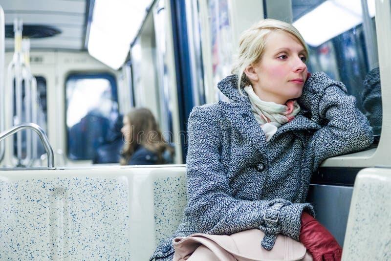 Jovem mulher que senta-se dentro de um vagão do metro imagem de stock