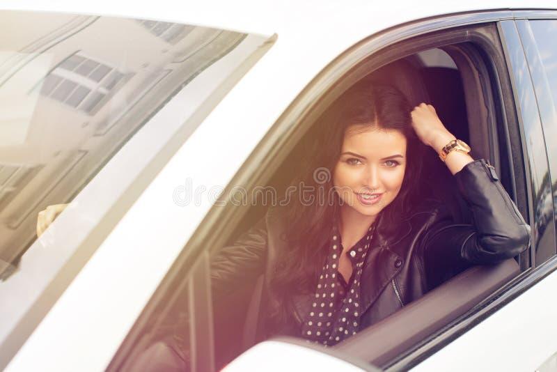 Jovem mulher que senta-se dentro do carro que sorri na câmera foto de stock