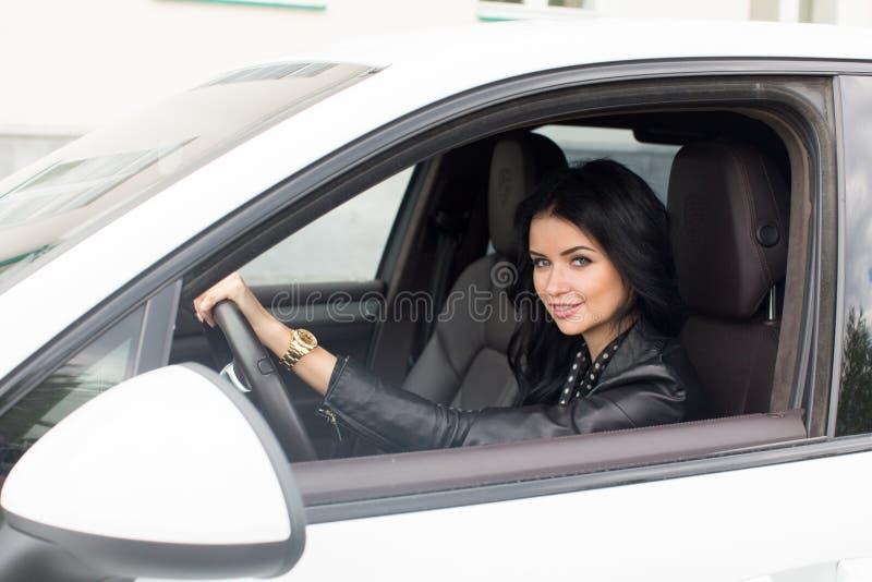 Jovem mulher que senta-se dentro do carro que sorri na câmera fotos de stock royalty free