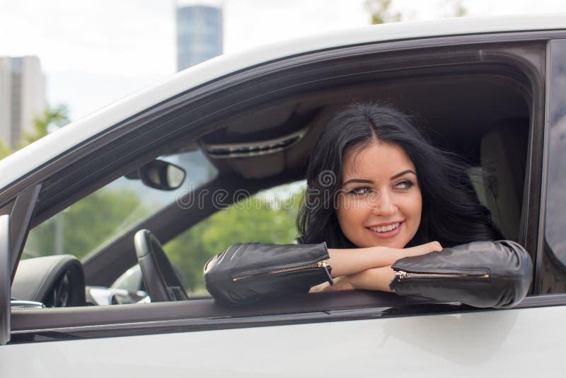 Jovem mulher que senta-se dentro do sorriso do carro imagens de stock royalty free