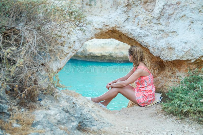 Jovem mulher que senta-se e que relaxa sob uma formação natural do arco da pedra calcária pelo Algarves, Portugal fotos de stock