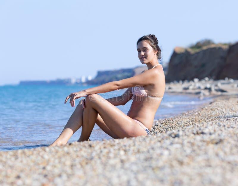 A jovem mulher que senta-se em seixos aproxima o mar fotografia de stock