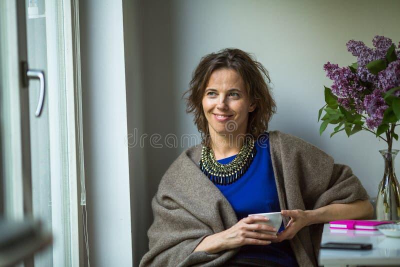 Jovem mulher que senta-se em sua casa perto da janela com um copo do chá em suas mãos fotografia de stock royalty free