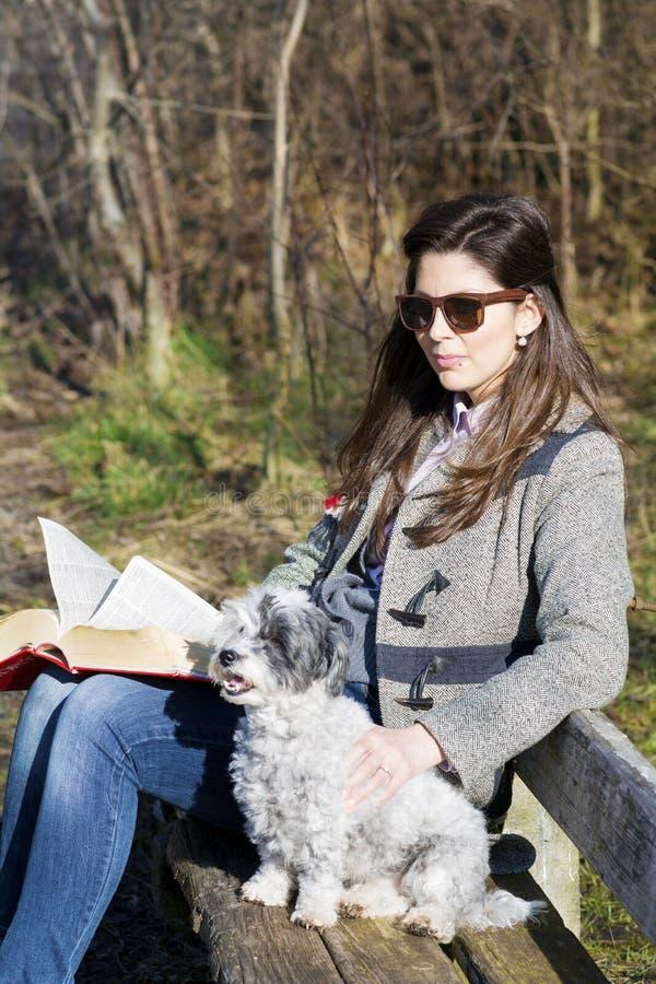 Jovem mulher que senta-se em um banco no parque do outono com seu cão foto de stock