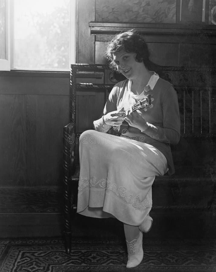 Jovem mulher que senta-se em um banco que joga o bandolim (todas as pessoas descritas não são umas vivas mais longo e nenhuma pro fotos de stock