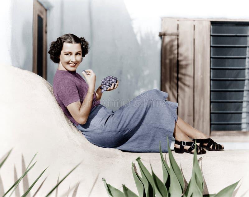 Jovem mulher que senta-se em um terraço que sorri e que come uvas (todas as pessoas descritas não são umas vivas mais longo e nen foto de stock