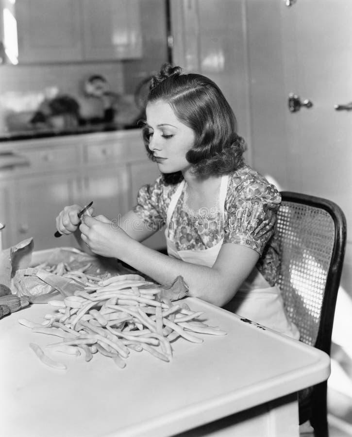 Jovem mulher que senta-se em uma cadeira e que corta feijões (todas as pessoas descritas não são umas vivas mais longo e nenhuma  imagem de stock