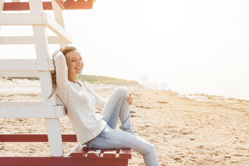Jovem mulher que senta-se na cadeira da salva-vidas da praia fotografia de stock
