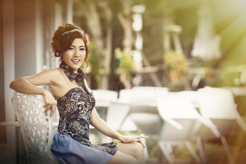 Jovem mulher que senta-se na cadeira na arcada exterior da compra, sorrindo fotografia de stock royalty free
