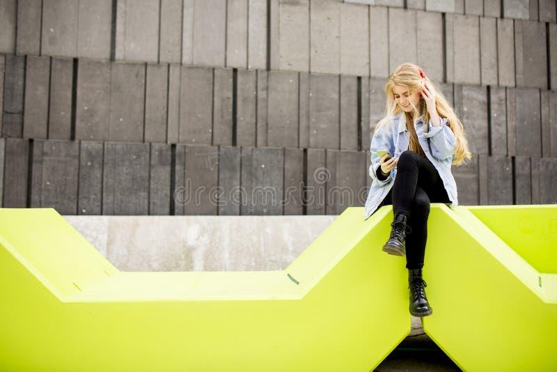 A jovem mulher que senta-se na cidade e usa um telefone celular imagem de stock