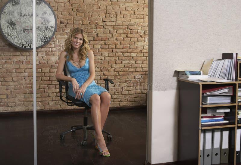 Jovem mulher que senta-se na entrada do escritório foto de stock