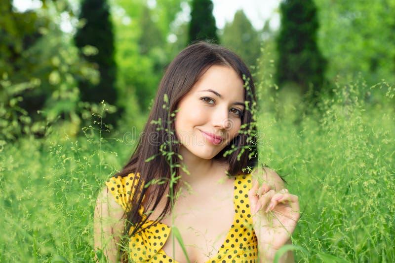 Jovem mulher que senta-se na grama imagem de stock