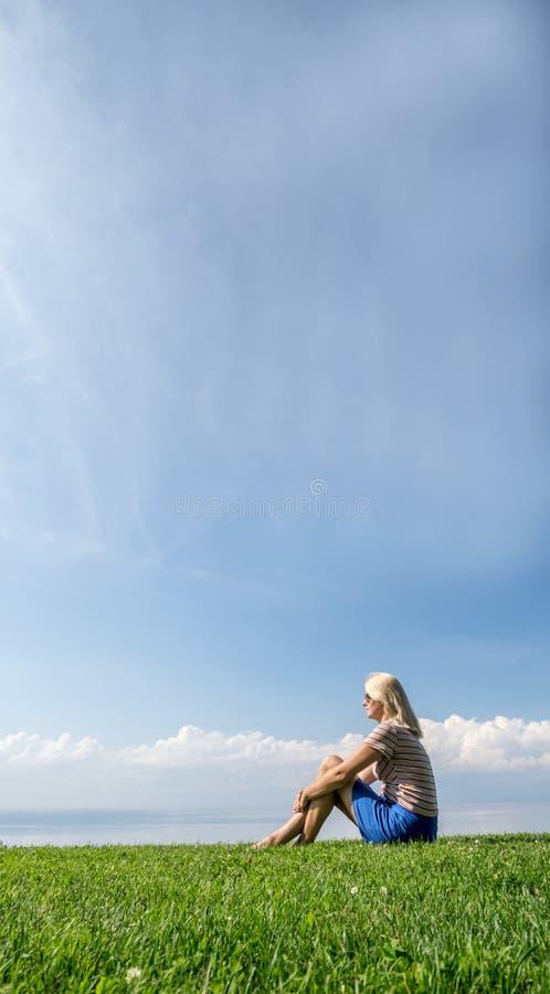 Jovem mulher que senta-se na grama em um lugar pitoresco, paisagem idílico do verão imagens de stock
