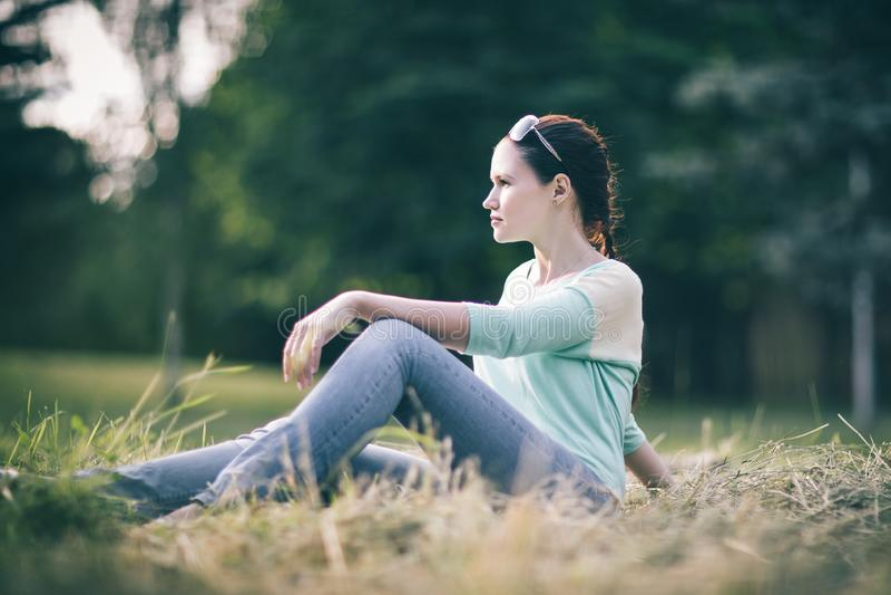 Jovem mulher que senta-se na grama no parque imagem de stock royalty free