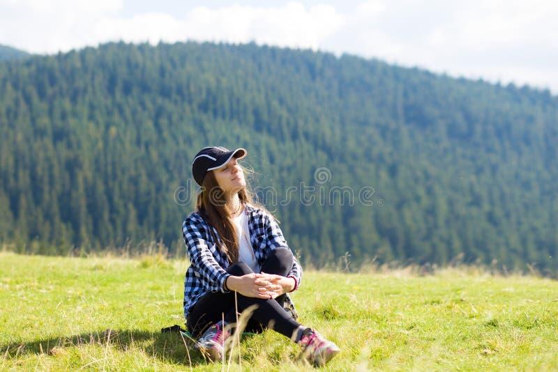 Jovem mulher que senta-se na parte superior da montanha que olha pacificamente em nuvens ao nível do mar da manhã fotografia de stock royalty free