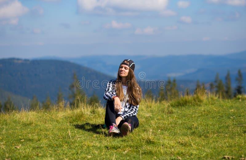 Jovem mulher que senta-se na parte superior da montanha que olha pacificamente em nuvens ao nível do mar da manhã imagens de stock royalty free