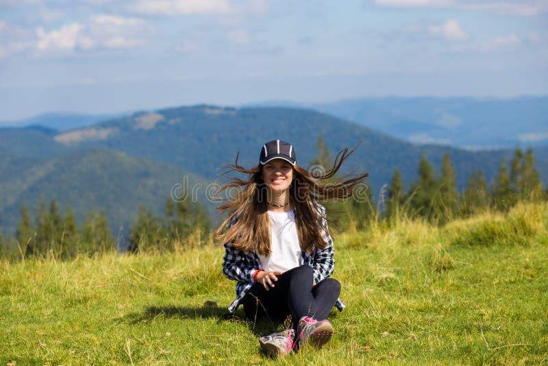 Jovem mulher que senta-se na parte superior da montanha que olha pacificamente em nuvens ao nível do mar da manhã imagem de stock royalty free