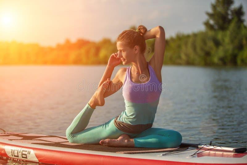 Jovem mulher que senta-se na placa de pá, pose praticando da ioga Fazendo a ioga exercite na placa do sup, resto ativo do verão imagens de stock royalty free