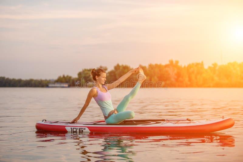 Jovem mulher que senta-se na placa de pá, pose praticando da ioga Fazendo a ioga exercite na placa do sup, resto ativo do verão foto de stock