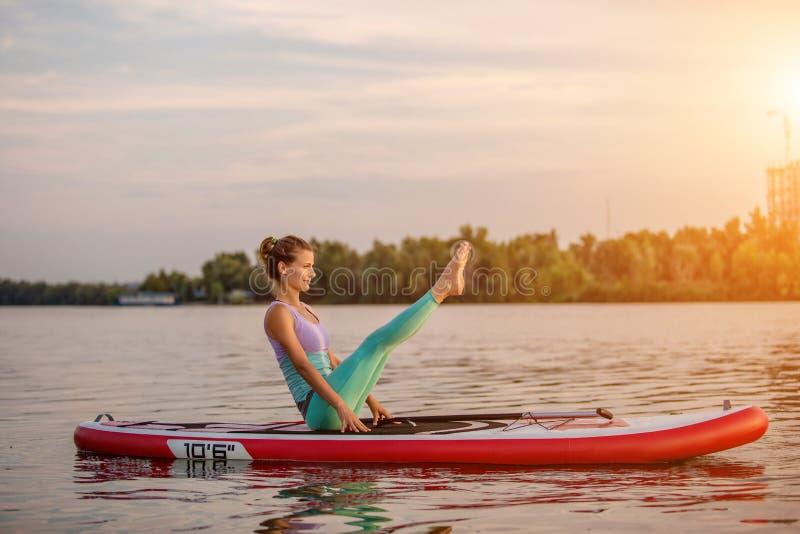Jovem mulher que senta-se na placa de pá, pose praticando da ioga Fazendo a ioga exercite na placa do sup, resto ativo do verão imagens de stock