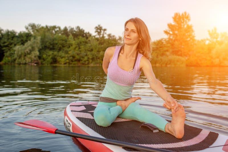 Jovem mulher que senta-se na placa de pá, pose praticando da ioga Fazendo a ioga exercite na placa do sup, resto ativo do verão fotografia de stock