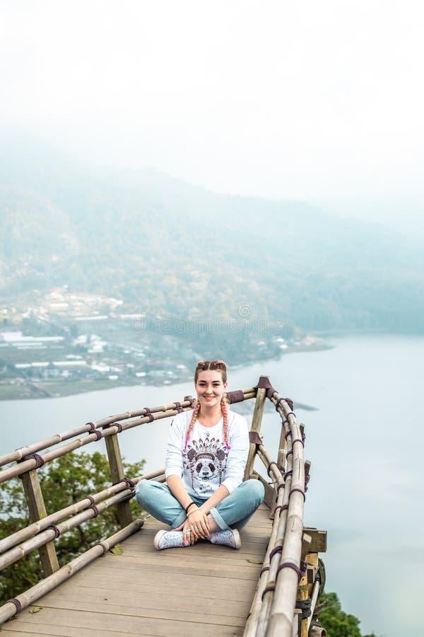 Jovem mulher que senta-se na ponte de madeira na parte superior da montanha com um fundo tropical do lago Ilha de Bali fotos de stock