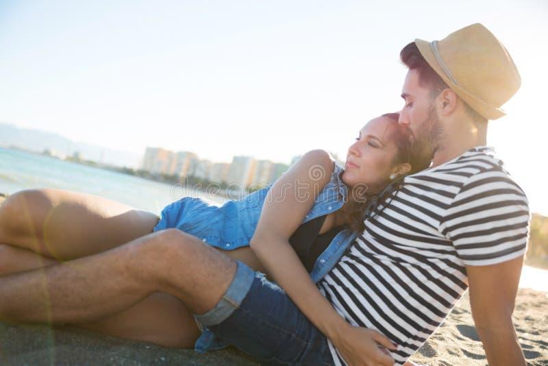 Jovem mulher que senta-se na praia com o noivo que afaga com ele fotos de stock