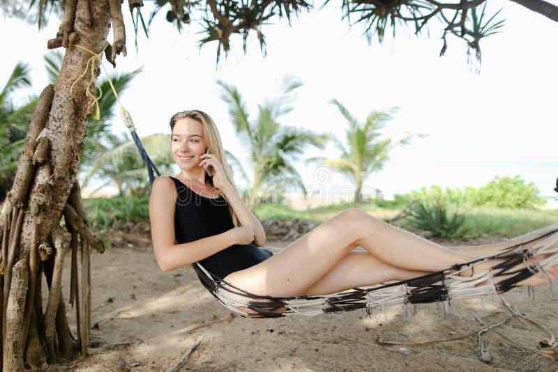 Jovem mulher que senta-se na rede com palmas e areia no fundo, roupa de banho preto vestindo imagens de stock royalty free