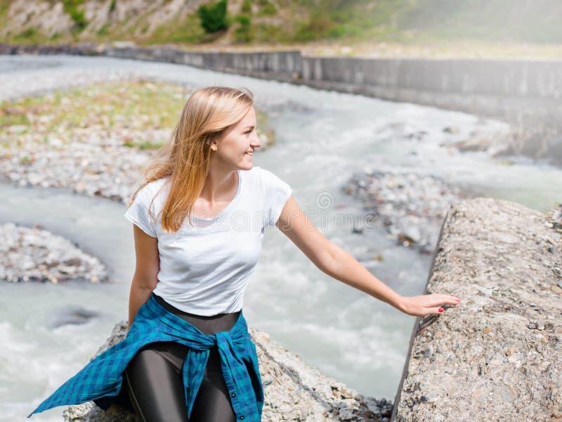 Jovem mulher que senta-se na rocha no rio rápido da montanha e que espirra no fundo exterior do espaço da cópia do verão ou do ou fotos de stock
