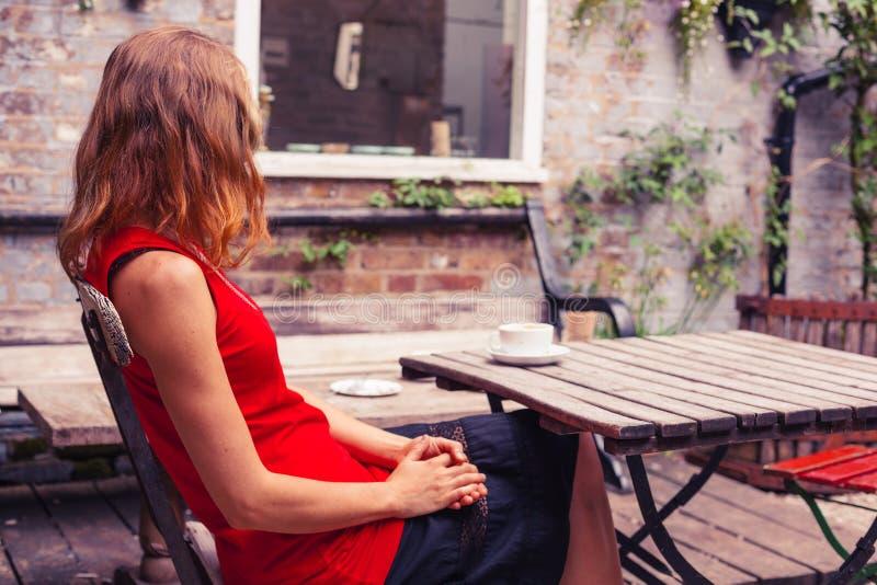 Jovem mulher que senta-se na tabela no jardim imagem de stock