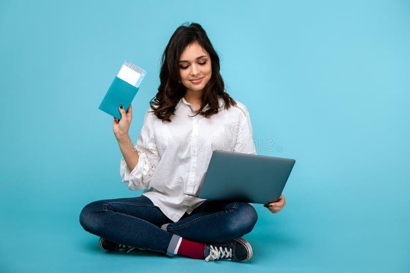 Jovem mulher que senta-se no assoalho com tichets da compra do port?til e do passaporte em linha fotografia de stock royalty free