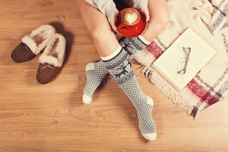 Jovem mulher que senta-se no assoalho de madeira com xícara de café, manta, cookie e livro Close-up dos pés fêmeas em peúgas morn foto de stock