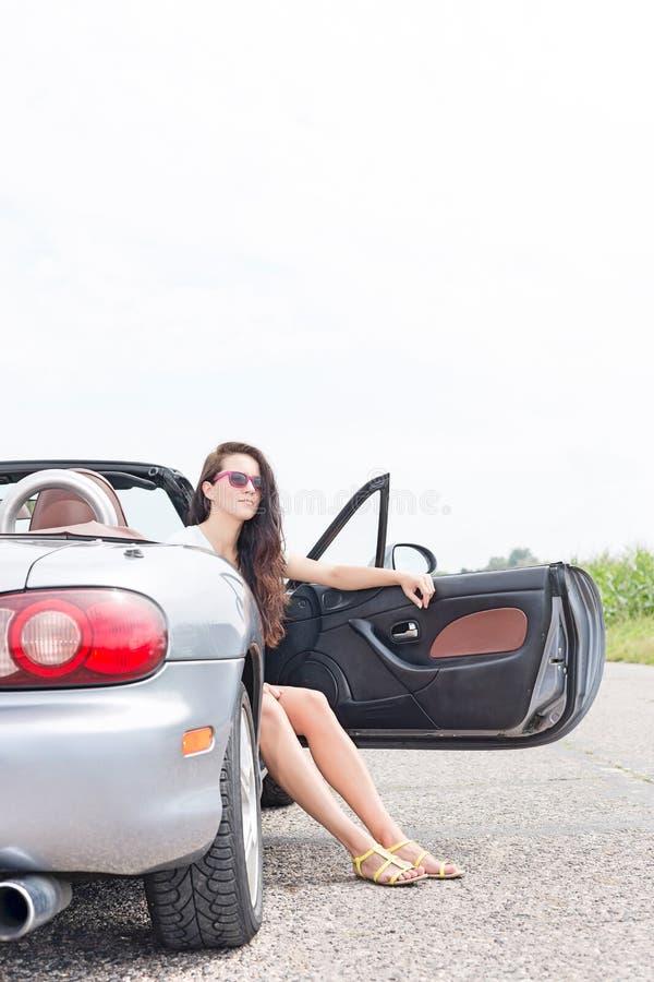 Jovem mulher que senta-se no convertible na estrada secundária contra o céu claro imagem de stock