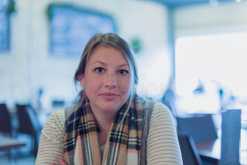 A jovem mulher que senta-se no restaurante, braços cruzou a vista da câmera imagens de stock