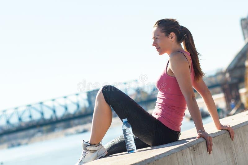 Jovem mulher que senta-se no riverbank fotografia de stock