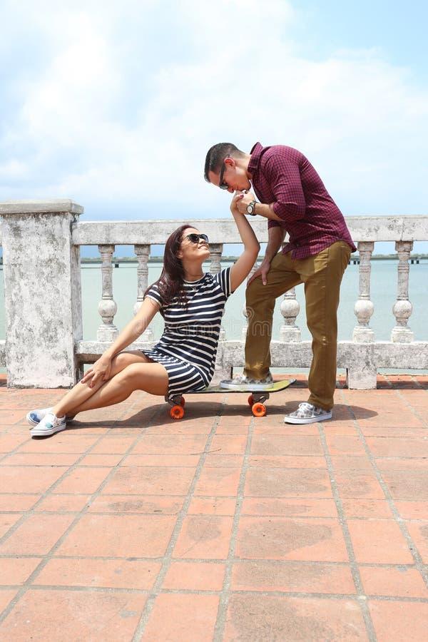 Jovem mulher que senta-se no skate com o forehea de beijo do noivo imagem de stock royalty free