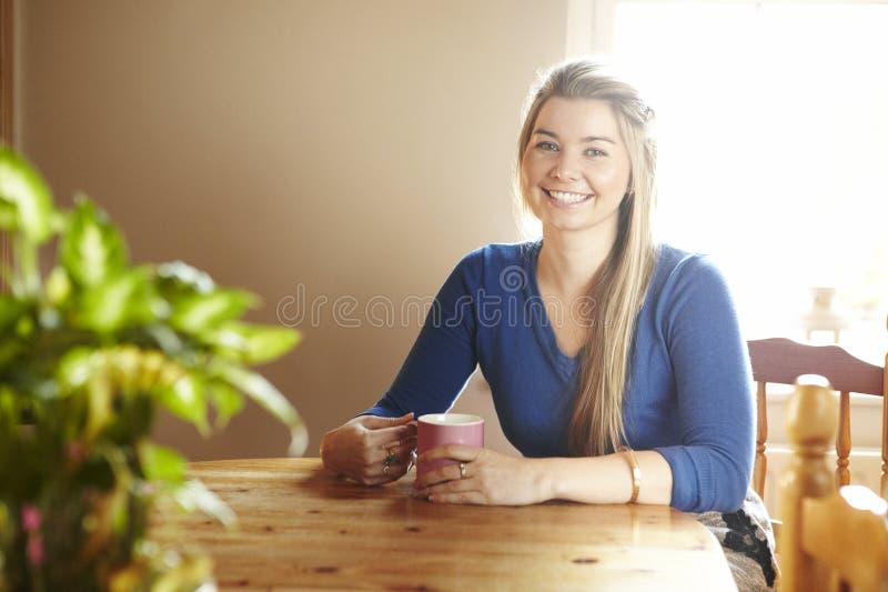 Jovem mulher que senta-se no sorriso da tabela imagens de stock royalty free